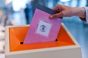 Hånd som legger en stemmeseddel inn i en valgurne.