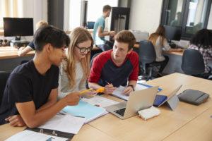 Tre elever på videregående skole sitter sammen i klasserommet og snakker med hverandre.