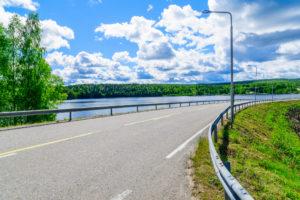 Fylkesvei som svinger langs en elv om sommeren. Himmel med skyer i bakgrunnen.